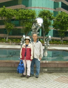 Writer, wife and a sculpture of dolphins behind them
