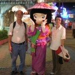 Writer and his wife posing with the pretty cartoon character at Carnival Village